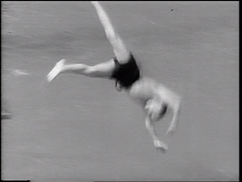 b/w 1937 tilt down boy with bathing suit diving into swimming pool - 室外プール点の映像素材/bロール