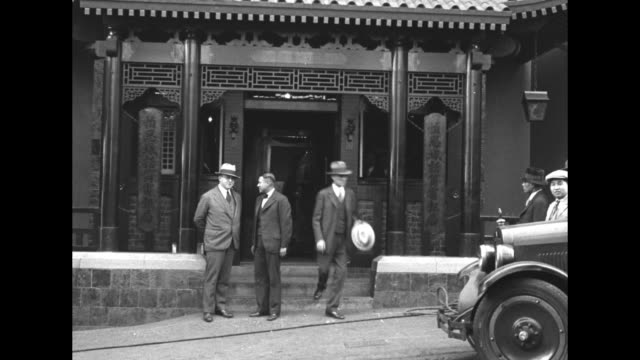vídeos de stock, filmes e b-roll de tilt down building in pagoda style that houses exchange, people standing on sidewalk in front of building / chinese-american women inside working at... - moving past