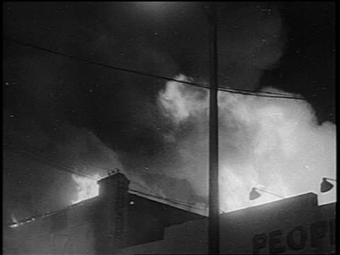 B/W 1965 tilt down building on fire during Watts race riots / Los Angeles / newsreel