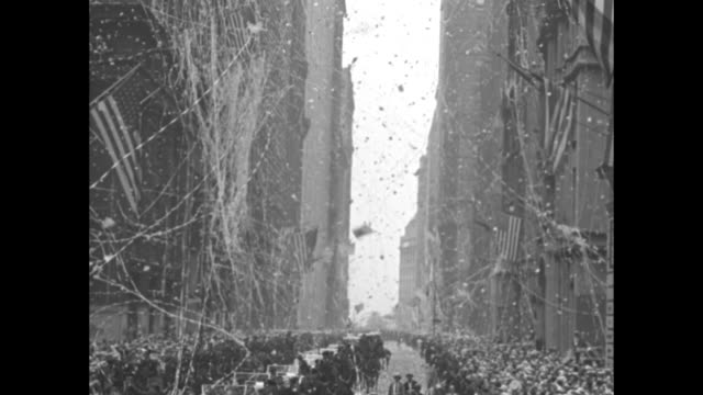 Tilt down buildings and ticker tape falling from Manhattan buildings to motorcade driving along in parade down street / moving camera shot of Wiley...