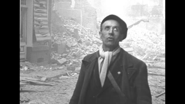 tilt down burning building hit by bomb / elderly woman walking down street with cane past wreckage from bombing / two shots of man walking down... - deutsches militär stock-videos und b-roll-filmmaterial