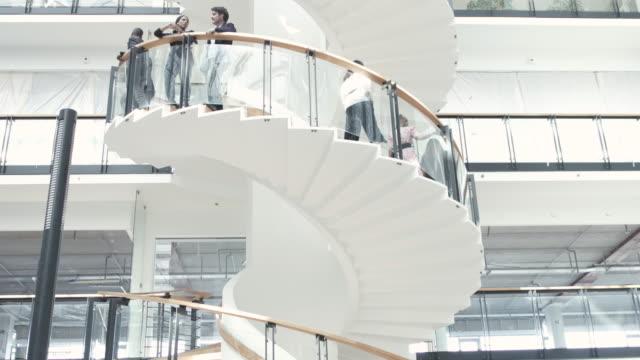 Tilt down, businesspeople walk down spiral staircase