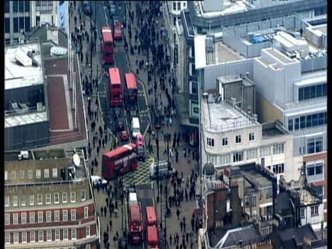 Tilt down busy Oxford Street zoom in to people red buses and black taxi cabs