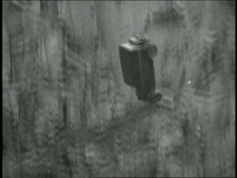 b/w 1934 tilt down car driving off cliff / newsreel - klippe stock-videos und b-roll-filmmaterial