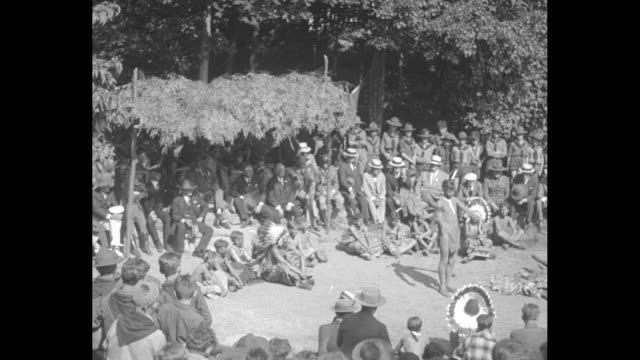 stockvideo's en b-roll-footage met tilt down circle of seated boy scouts and men with boy scout standing in middle dressed as an native american during gathering at bear mountain camp... - al smith
