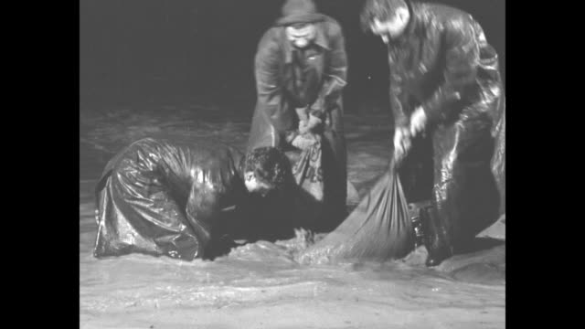 tilt down civilian conservation corps workers wearing raincoats and boots fill and place sandbags at night / ccc workers march carrying sandbags over... - civilian conservation corps stock-videos und b-roll-filmmaterial