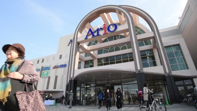 Tilt down close up from signage displaying 'Ario' to shoppers and pedestrians walking past an Ito Yokado Co Ario shopping center owned by Seven i...