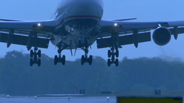 blue tilt down close up pan large airliner approaching + landing on runway - generic location stock videos & royalty-free footage