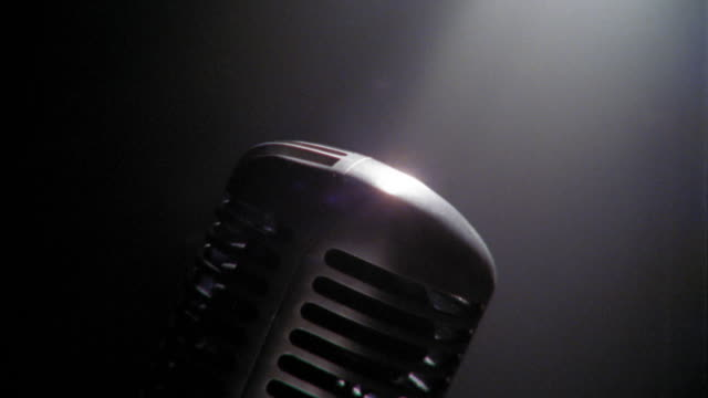 Tilt down close up microphone in spotlight