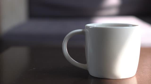 vídeos y material grabado en eventos de stock de incline hacia abajo cerca blanco taza taza y sofá como fondo con espacio de copia - un solo objeto
