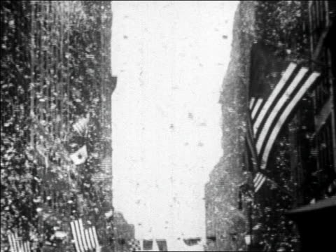 b/w 1927 tilt down confetti falling over marching band in ticker tape parade for lindbergh / newsreel - 1927 stock videos & royalty-free footage