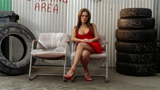 "tilt down corrugated metal wall with ""smoking area"" spraypainted on wall to woman in red dress waiting on chair between tires / los angeles, california - cross legged stock videos and b-roll footage"