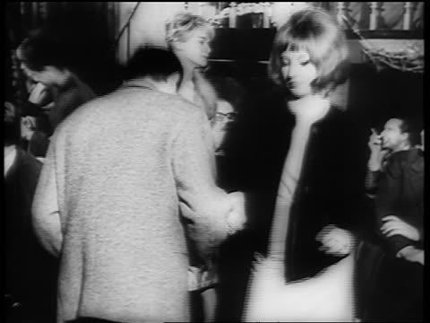 B/W 1961 tilt down couple dancing the Twist on dance floor / newsreel