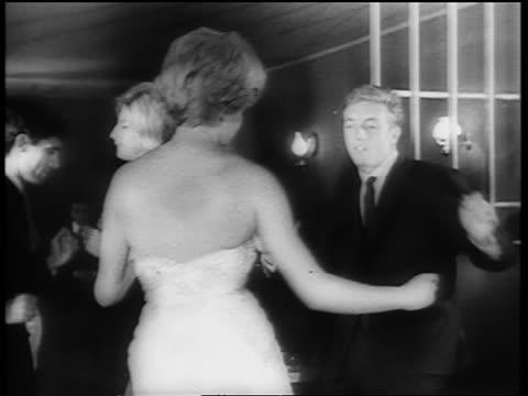 B/W 1961 tilt down couple dancing the Twist together on dance floor / newsreel