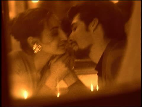 stockvideo's en b-roll-footage met tilt down couple holding hands + kissing in restaurant / france - heteroseksueel koppel