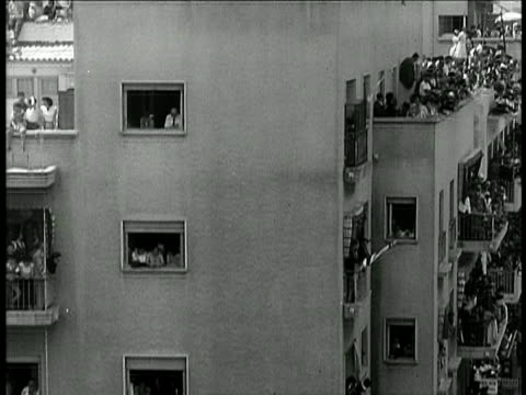 vídeos de stock, filmes e b-roll de b/w 1948 tilt down crowd gathered in building in streets to hear speech / documentary - 1948