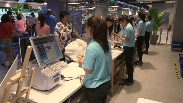 Tilt down customers browse live seafood in an Alibaba Group Holding Ltd Hema Store in Shanghai China on Tuesday Sept 12 A cashier waits for customers...