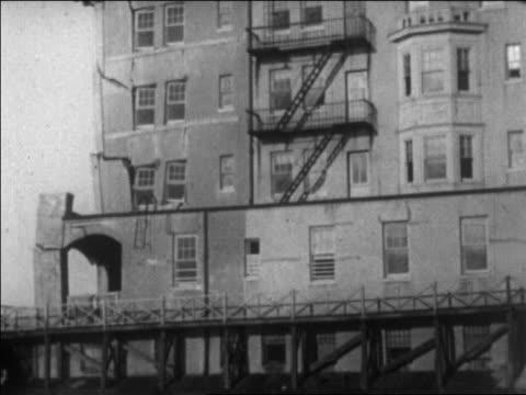 tilt down damaged hotel on beach / long beach, california / newsreel - 1926 stock videos & royalty-free footage