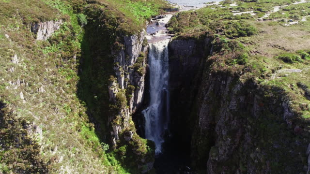 tilt down drone shot showing a waterfall, scottish highlands, united kingdom - rock face stock videos & royalty-free footage