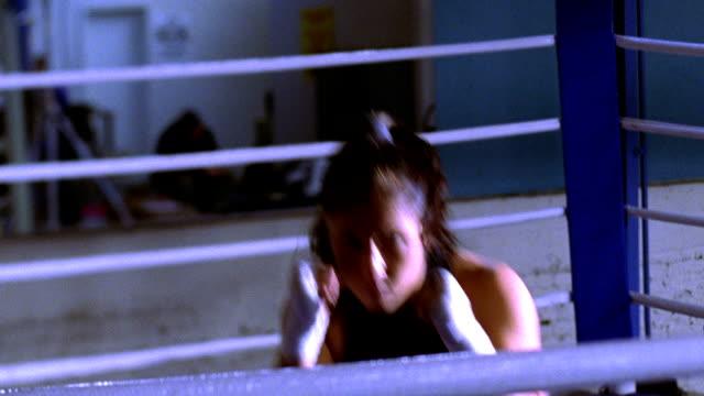 vídeos de stock, filmes e b-roll de ms tilt down female boxer facing camera shadow boxing with taped hands in ring - posição de combate