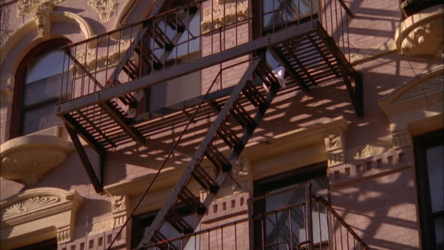 tilt down fire escapes on building facade / nyc - fire escape stock videos & royalty-free footage