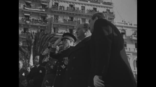 Tilt down French Prime Minister Edouard Daladier walks up steps carrying flowers past dignitaries and followed by entourage / CU Daladier with...