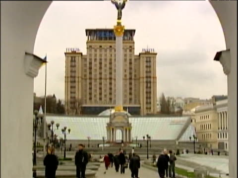 tilt down from archway to city square pedestrians pass stand selling ukrainian flags kiev - 2000s style stock videos & royalty-free footage