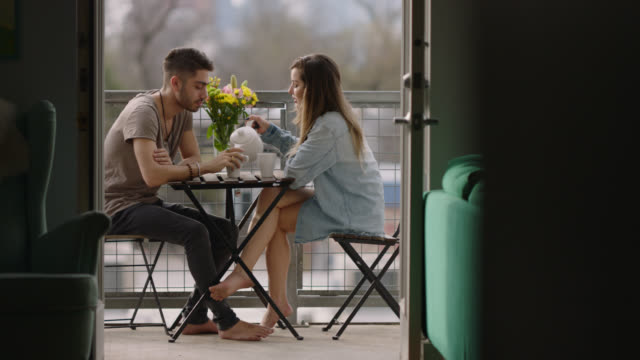 tilt down from austin, texas skyline as a young couple share an intimate moment while having a morning cup of tea on balcony. - ティーポット点の映像素材/bロール