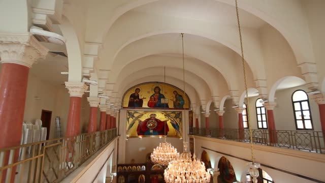 tilt down from balcony reveals sparsely populated pews in church ongoing church service in lebanon - begriffssymbol stock-videos und b-roll-filmmaterial