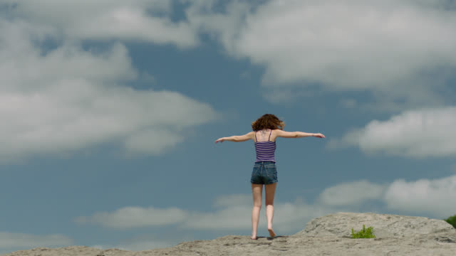 ws slo mo. tilt down from blue sky as barefoot girl spins and dances across rocky mountaintop. - mindfulness stock videos & royalty-free footage