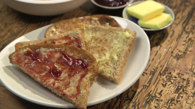 tilt down from breakfast cereal to buttered toast with jam on a wooden table. - spread food stock videos and b-roll footage