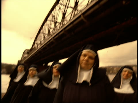 pan tilt down from bridge to ms group of nuns standing under bridge bobbing heads to beat of music / prague - nun stock videos & royalty-free footage