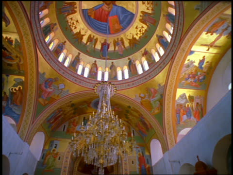 stockvideo's en b-roll-footage met tilt down from brightly colored rotunda to rear view guards standing around altar in church / greece - altaar