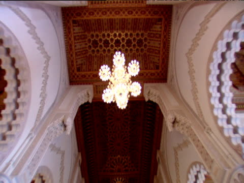 Tilt down from ceiling of mosque to interior with columns and arches ornate brass lamps in foreground Hassan II Mosque Casablanca