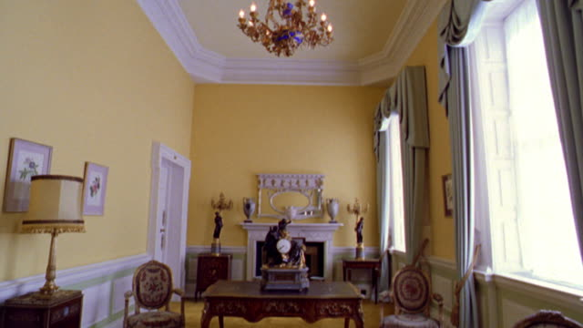tilt down from ceiling with chandelier to center of yellow room with desk in Dublin Castle / Dublin, Ireland