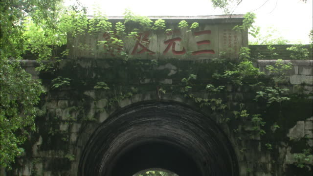 tilt down from chinese script on sign above arch in ancient city walls to car and bicycles passing beneath - chinese script stock videos & royalty-free footage