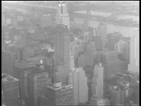 b/w 1930 tilt down from chrysler building to construction worker on girder on empire state building / nyc - 1930 stock videos & royalty-free footage