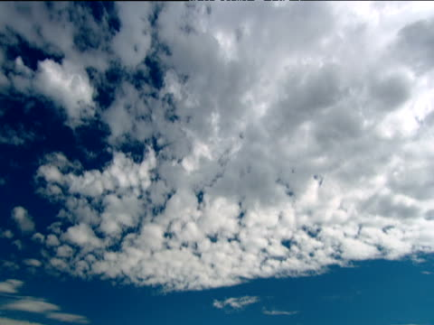 tilt down from cloud in blue sky to table mountain with layer of cloud resting on top waves lap onto beach in foreground - altocumulus stock videos and b-roll footage