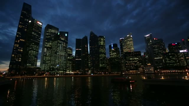 tilt down from clouds in sky to commercial buildings on skyline in the central business district at dusk in singapore on monday dec 9 pan lr... - singapore flyer stock videos and b-roll footage