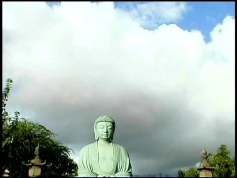 tilt down from clouds in the sky to a buddha statue in a park. - weibliche figur stock-videos und b-roll-filmmaterial