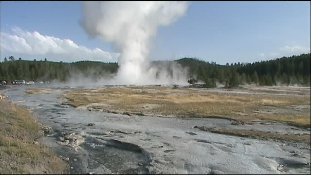 tilt down from column of water and steam rising from great fountain geyser, pan right to water flowing down creek, yellowstone national park, wyoming - geyser video stock e b–roll
