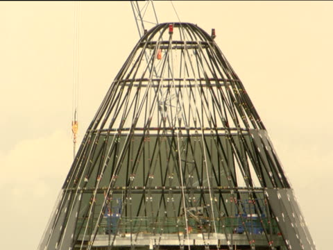 tilt down from crane to top of 30 st mary axe building (aka 'gherkin') under construction london; 2002 - erezione video stock e b–roll