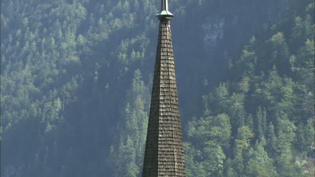 tilt down from cross to clock on wooden tower of evangelical church on banks of hallstattersee, hallstatt - österreichische kultur stock-videos und b-roll-filmmaterial