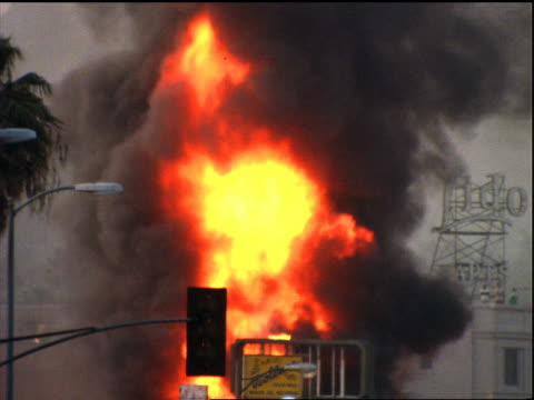 tilt down from dark smoke to fire on roof, zoom out to street + buildings / los angeles riots - 1992年点の映像素材/bロール