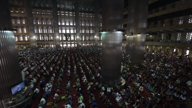 vídeos de stock e filmes b-roll de tilt down from dome inside istiqlal mosque to men praying in the hall, pan l-r men praying in the hall, r-l men praying in the hall, tilt up from men... - mesquita