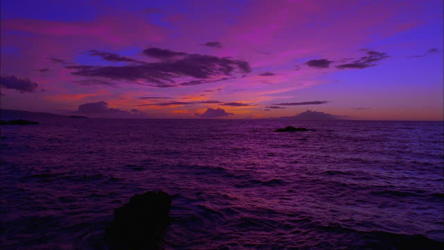 vidéos et rushes de tilt down from dramatic blue, pink and orange sky to rippling sea at sunset, hawaii available in hd. - violet