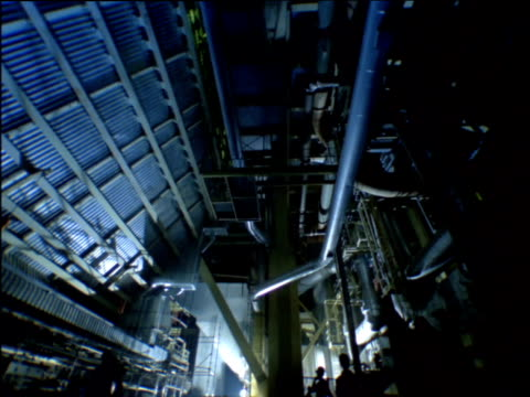 vídeos de stock e filmes b-roll de tilt down from factory ceiling to industrial workers carrying equipment across floor - enfeites para a cabeça