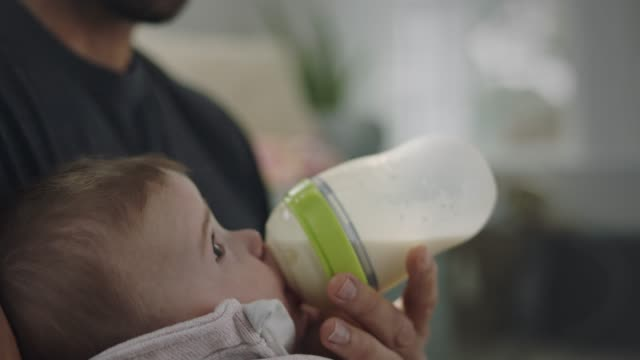 vídeos de stock e filmes b-roll de cu slo mo. tilt down from father's smiling face as infant daughter nurses a bottle of milk. - biberão