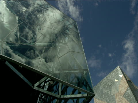 Tilt down from glass exterior of arts centre to entrance formed by complex steel structure Federation Square Melbourne