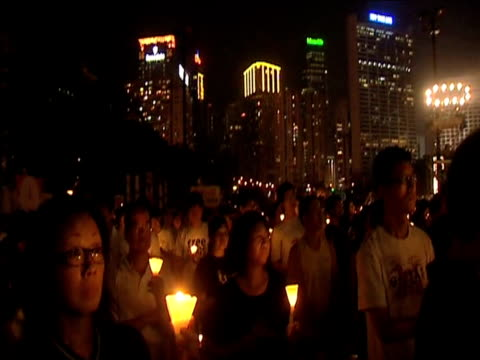 tilt down from high rise building at night to large crowd holding lanterns during commemorative ceremony marking 20th anniversary of tiananmen square... - tiananmen square massacre stock videos & royalty-free footage